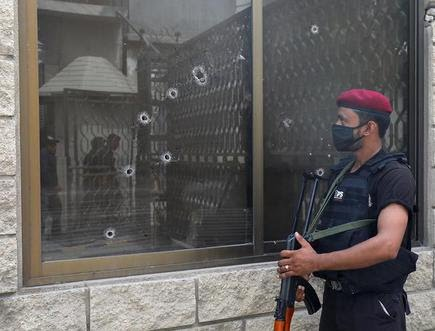A police officer stands guard next to a bullet riddled window at the Pakistan Stock Exchange building after an attack in Karachi, Pakistan on June 29, 2020.
