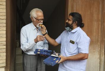 A man offers sweets to Balachandran Gopalan, U.S. Vice-President-elect Kamala Harris' maternal uncle, in New Delhi on November 8, 2020.