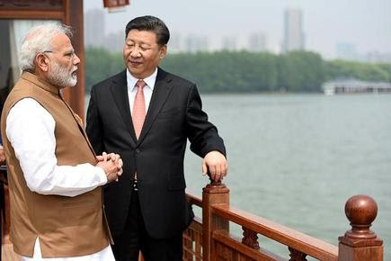 This April 28, 2018 file picture shows Prime Minister Narendra Modi and Chinese President Xi Jinping interacting in a house boat, at East Lake, in Wuhan.