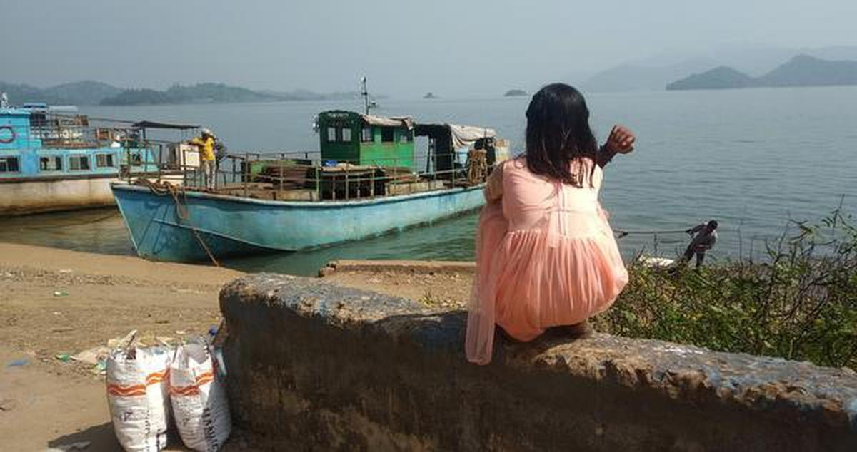 A young girl waits for the boat to return home to Swabhiman Anchal.