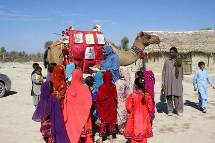 Children stand next to Roshan the camel, who brings books, in Mand, Pakistan