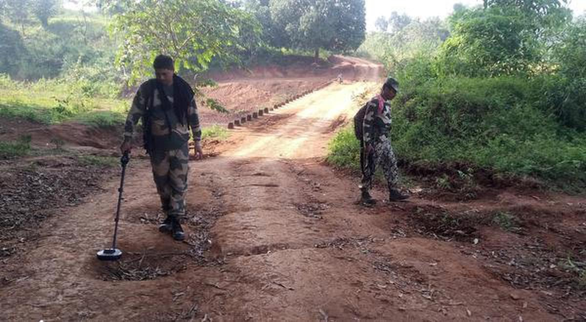 BSF men check for landmines on a village road